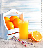 Glass of orange juice and fresh oranges in wooden box on wooden table on wooden wall background — Stock Photo