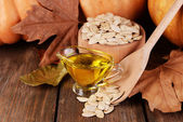 Pumpkin seed oil in glass sauce-boat and fresh pumpkin on wooden background — Stock Photo