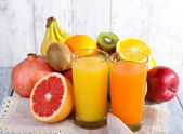 Fruit and vegetable juice and fresh fruits on napkin on wooden table on wooden wall background — Stock Photo