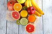 Fruit and vegetable juice and fresh fruits on napkin on wooden background — Stock Photo