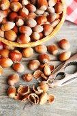 Hazelnuts in wicker basket on wooden background — Stock Photo