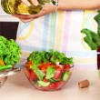 Woman pouring olive oil in vegetable salad in kitchen — Stock Photo #56383363