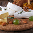 Camembert cheese on paper, grapes, nuts and honey in glass bowl on on cutting board on wooden background — Stock Photo #56384197