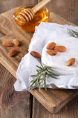 Camembert cheese on paper, honey in glass bowl and nuts on cutting board on wooden background — Foto Stock