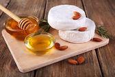 Fromage camembert, le miel dans le bol en verre sur planche à découper sur fond en bois — Photo
