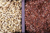 Flax seeds and groats in wooden box closeup — Stok fotoğraf