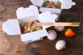 Chinese noodles in takeaway boxes with mushrooms and parsley on wooden background — Stock Photo