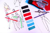 Sketches of clothes and fabric samples on table — Stock Photo
