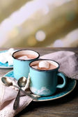 Cups of tasty hot cocoa, on wooden table, on light background — Stock Photo