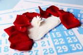 Sanitary pads, white Berber and rose petals on red calendar background — Stock Photo