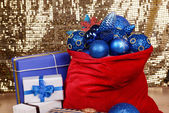 Red bag with Christmas toys and gifts on fabric background — Stock Photo