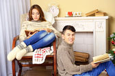 Happy couple relaxing with book at home — Stock Photo