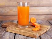 Glass of carrot juice and fresh carrot on cutting board on wooden table on wooden wall background — Foto Stock