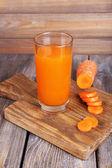 Verre de jus de carotte et carotte fraîche sur une planche à découper sur la table en bois sur fond de mur en bois — Photo