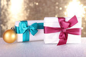 Gift boxes with vinous and blue ribbons and Christmas tree toy on table on shiny background — Stock Photo