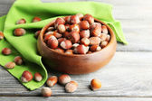 Hazelnuts in wooden bowl, on napkin on wooden background — Stock Photo