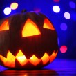 Halloween Pumpkin on table on dark color background with multicolor lights — Stock Photo #56463499