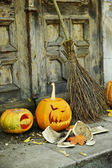 Pumpkin and broom for holiday Halloween on old wooden door background — Stock Photo