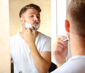Young man shaving his beard in bathroom — Foto Stock