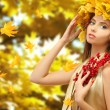 Beautiful young woman with yellow autumn wreath outdoors — Stock Photo #56591307
