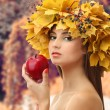 Beautiful young woman with yellow autumn wreath and apple outdoors — Stock Photo #56591321