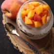 Healthy breakfast - yogurt with fresh peach and muesli served in glass jar, on wooden background — Stock Photo #56593303