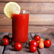 Glass of tomato juice with lemon and fresh tomatoes on wooden table on wooden wall background — Stock Photo #56595647