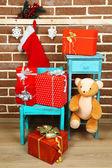 Kerstcadeaus op stoel op bruin bakstenen muur achtergrond — Stockfoto
