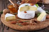 Camembert cheese on paper, grapes, nuts and honey in glass bowl on on cutting board on wooden background — Stock Photo