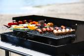 Sausages and vegetables on barbecue grill, close-up — Stock Photo