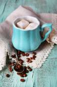 Cup of coffee with marshmallow and napkin on wooden table — Stock Photo
