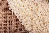 Rice on sackcloth background — Stock Photo