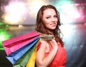 Beautiful young woman with shopping bags on bright background — Foto Stock