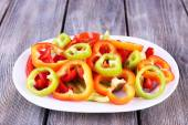 Sliced pepper on oval plate on wooden background — Stock Photo