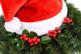 Leaves of mistletoe with Christmas hat — Foto Stock