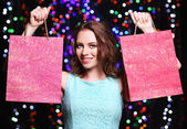 Beautiful young woman with shopping bags on bright lights background — Стоковое фото