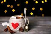 Tasse leckeren heißen Kakao auf Holztisch, auf glänzendem Hintergrund — Stockfoto