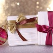 Gift boxes with vinous and golden ribbons and bows and Christmas tree toy on table on shiny background — Stock Photo #56791503