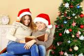 Young couple with book sitting in rocking chair near Christmas tree — Stock Photo