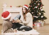 Young couple with gifts, sitting on carpet, at home — Stock Photo