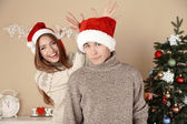 Nice love couple near Christmas tree. Woman and man celebrating Christmas — Stock Photo