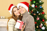 Young couple with gifts near Christmas tree — Stock Photo