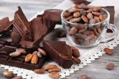 Cracked chocolate bar and cocoa beans — Stock Photo