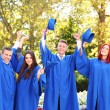 Students throwing graduation hats — Stock Photo #56865717