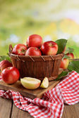 Sweet apples in wooden basket on table on bright background — Stock Photo
