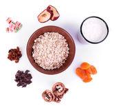 Bowl of oatmeal, mug of yogurt, dried apricots and walnuts isolated on white — Стоковое фото