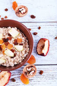 Bowl of oatmeal, walnuts, dried apricots — Stock Photo