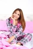 Belle jeune femme assise sur le lit — Photo