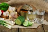 Bacon, fresh vegetables, boiled egg and bread on paper, glasses with vodka — Stockfoto
