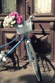 Old bicycle with flowers in metal basket — 图库照片